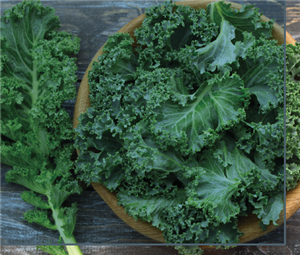 A wooden bowl with kale leaves in it.  One kale leaf is laying on the table