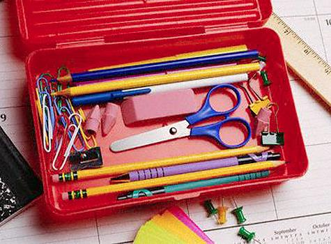 A picture of a school supply box. Inside the box are scissors, pencils, pens, erasers, paper clips, binder clips, etc