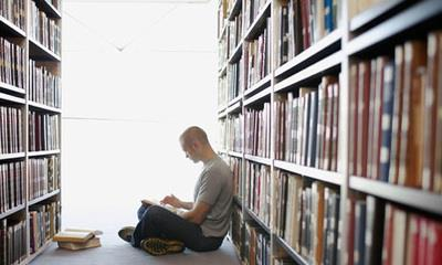 Student sitting among stacks reading